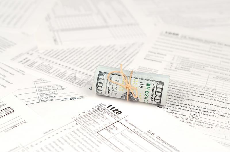 1120 U.S. Corporation income tax return form with roll of american dollar banknotes stock image
