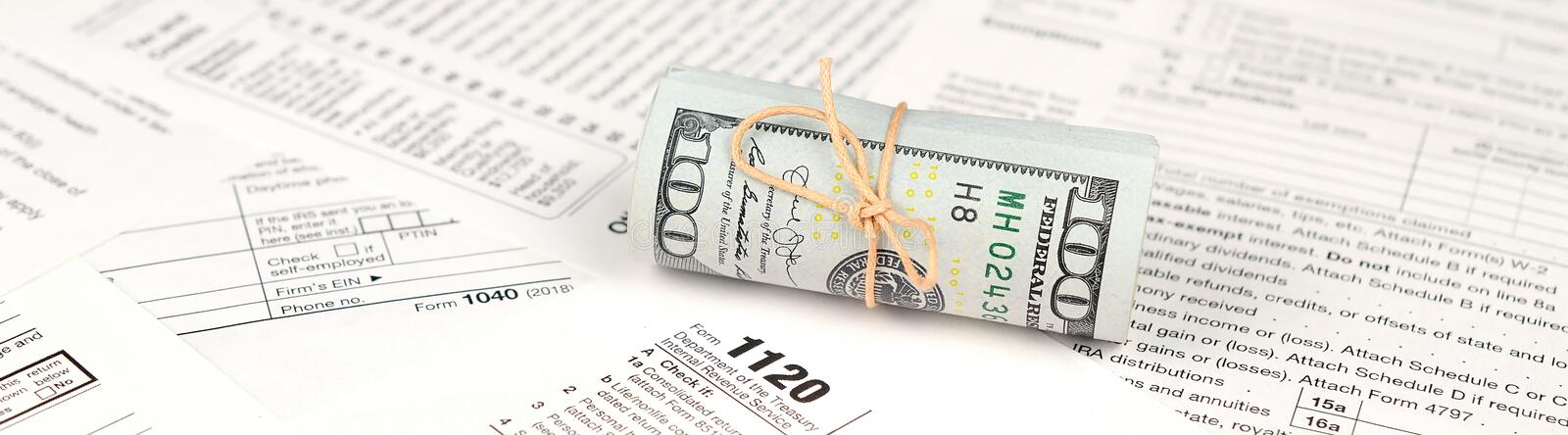 1120 U.S. Corporation income tax return form with roll of american dollar banknotes stock photo