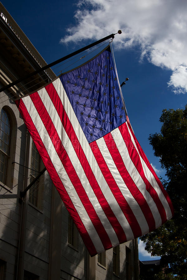 U.S. Flag at Harvard University. United States flag waving over the John Harvard Statue in Harvard Yard, the old heart of Harvard University campus in Cambridge royalty free stock images