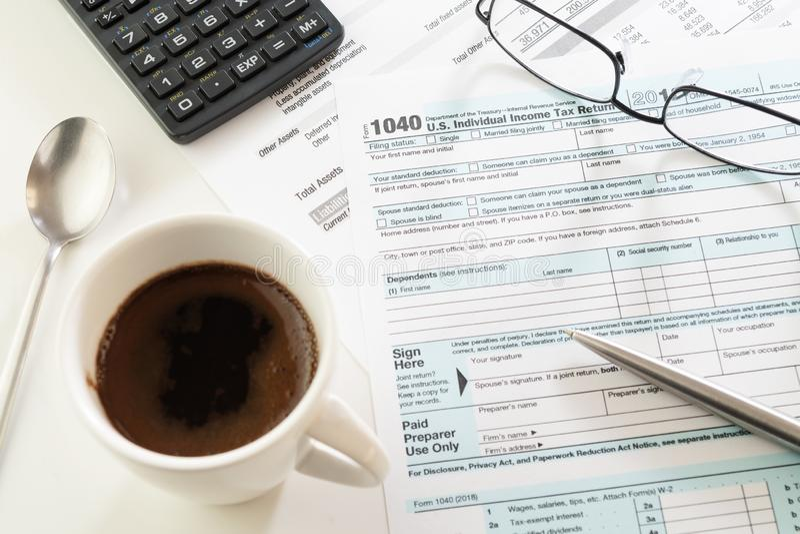 U S Formulário de declaração de rendimentos da renda, xícara de café, pena, calculadora e vidros fotos de stock