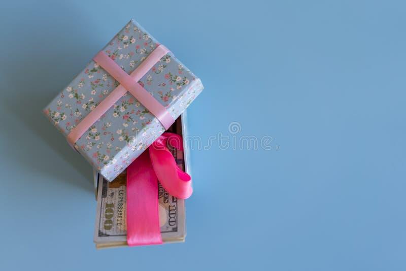 U S i dollari di banconote che risiedono nell'arco hanno decorato il contenitore di regalo Regalo e dollari aperti Contenitore di fotografie stock libere da diritti