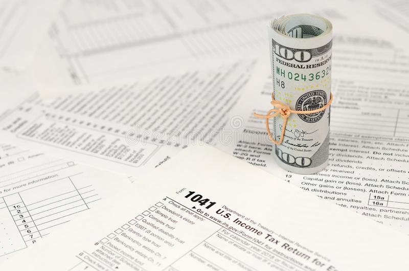 1041 U.S. Income tax return for Estates and Trusts form with roll of american dollar banknotes royalty free stock photo