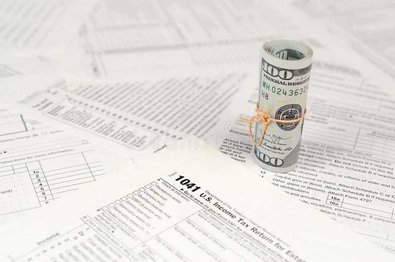1041 U.S. Income tax return for Estates and Trusts form with roll of american dollar banknotes stock photos