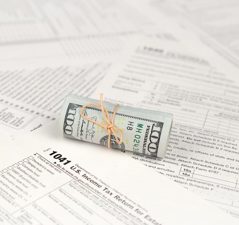 1041 U.S. Income tax return for Estates and Trusts form with roll of american dollar banknotes royalty free stock photography