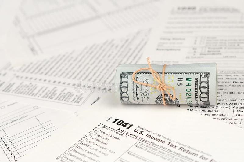 1041 U.S. Income tax return for Estates and Trusts form with roll of american dollar banknotes stock image