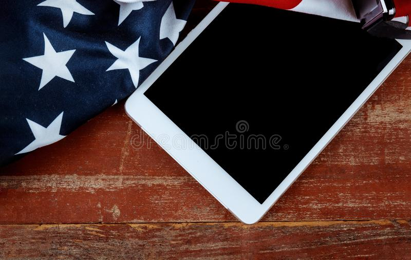 U.S national flag and e-tablet on wooden boards stock photography