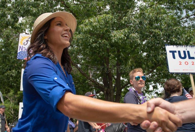 U S Rep Tulsi Gabbard schept handen tijdens de parade van 4 juli in Amherst, New Hampshire, VS, op 4 juli 2019 stock afbeelding