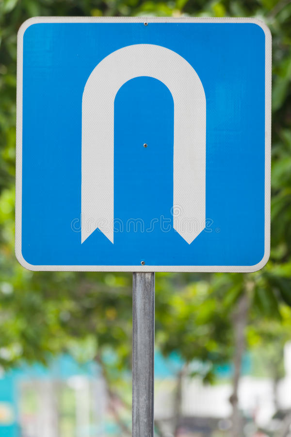 U-turn allowed road sign. A road sign indicates where traffic is allowed to make a u-turn royalty free stock photos