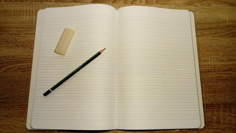 U-turn notebook with white blank sheets. On the left page are a graphic pencil and eraser royalty free stock photo