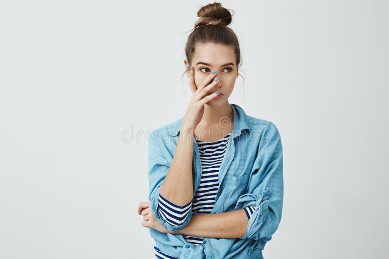 U verwarde me voor vrienden Portret van geïrriteerde jonge Europese vrouw in broodjeskapsel en denimoverhemd stock afbeeldingen