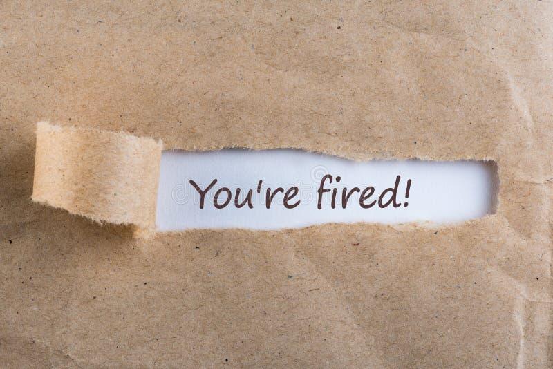 U wordt in brand gestoken Het bericht in brief of nota, die achter gescheurd pakpapier van enveloptekst u verschijnen wordt in br royalty-vrije stock fotografie