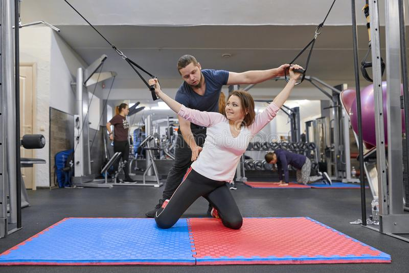 ??UA?28-03-2019 做在解压模拟器的成熟妇女锻炼有教练员修复的 体育生理治疗师 免版税库存照片
