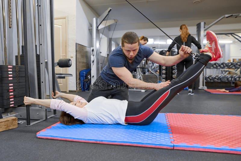 ??UA?28-03-2019 做在解压模拟器的成熟妇女锻炼有教练员修复的 体育生理治疗师 免版税图库摄影