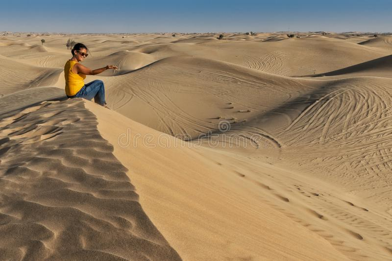 Photograph of woman sitting on top of a Dune in the desert of Abu Dhabi. UAE royalty free stock images