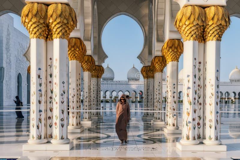 UAE/ABUDHABI 15 DEZ 2018 - posição da mulher na fachada da mesquita árabe fotografia de stock