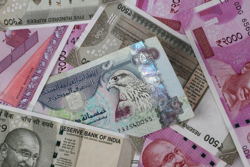 UAE Dirhams między Indiańskimi Nowymi rupii waluty banknotami obraz stock