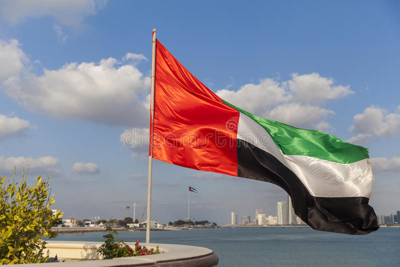 UAE flag waving with the background of Abu Dhabi Skyline as part of 43rd National Day celebrations. Daytime stock photography