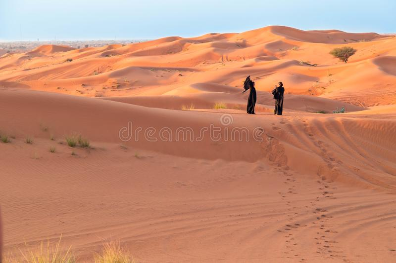 UAE Fujairah 2017.19.11 Safari jeeps tour. two women in the black orient Arab clothes photograph each other royalty free stock photography