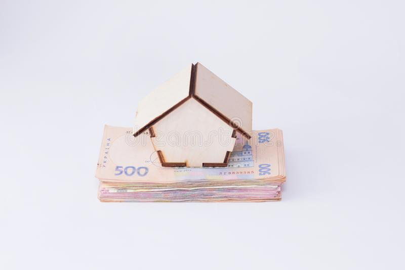 UAH hryvnia banknotes with wooden house isolated on white background. ukrainian money. concept of mortgage or buying home.  stock photography