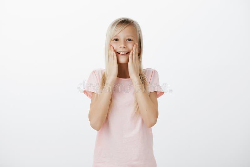 Uau, é realmente para mim Retrato da menina bonito surpreendida e surpreendida com cabelo louro, guardando as palmas em mordentes foto de stock