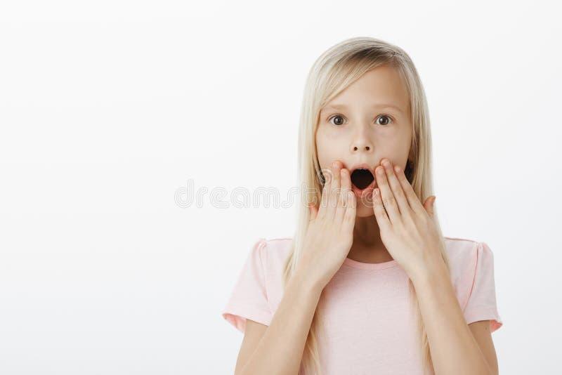 Uau, a criança chocou notícia surpreendente da audição sobre desenhos animados favoritos Tiro interno da filha loura feliz surpre imagem de stock royalty free