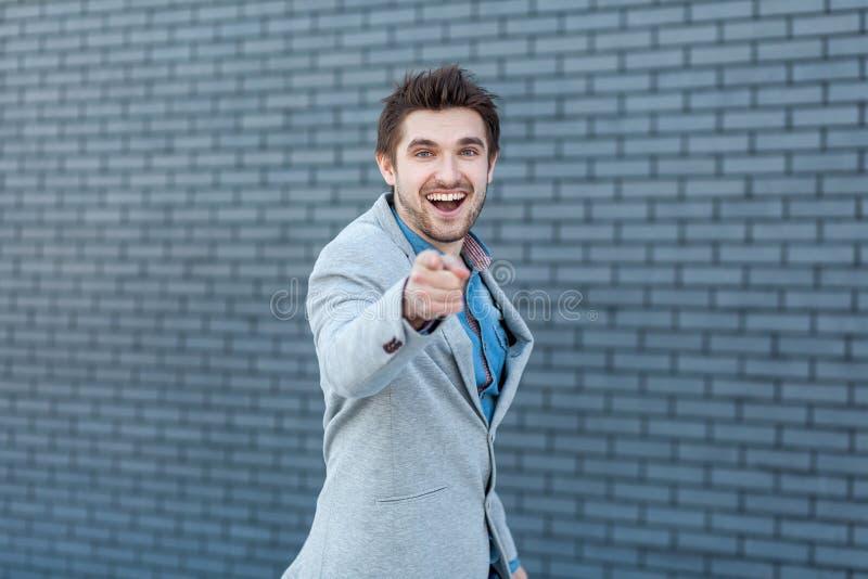 Uau, este é você? Retrato do homem farpado considerável surpreendido feliz no estilo ocasional que está, apontando e olhando a câ imagens de stock