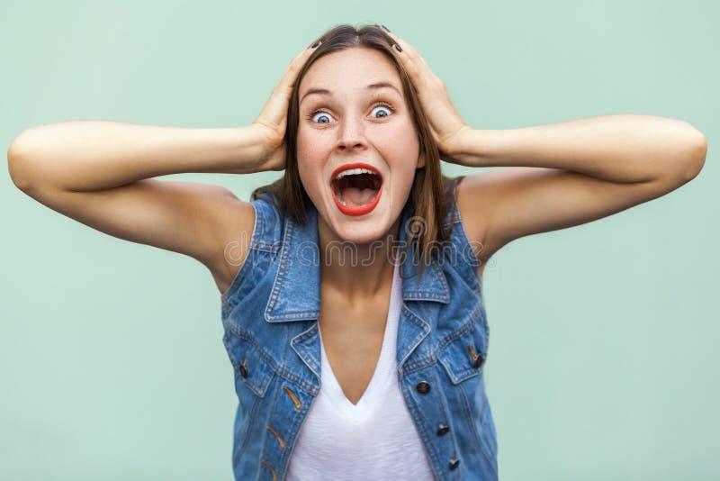 Uau! Não pode ser! Emoções e sentimentos positivos A menina bonita chocada e wounder, tocando em sua cabeça suas mãos e vista foto de stock
