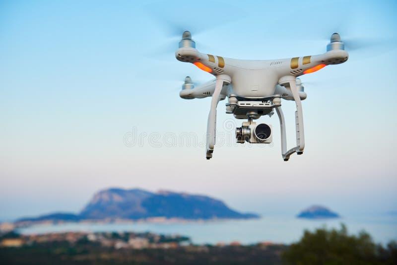 Uav de hommel met digitale camera hangt overzees eiland stock afbeeldingen