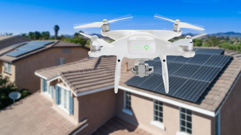 UAV Drone Inspecting Solar Panels On Large House. UAV Drone Inspecting Solar Panels On a New Large House stock images