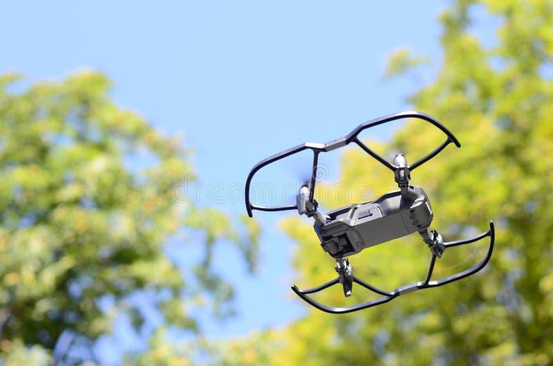 Uav-surrhelikoptern med den digitala kameran flyger nära de gröna träden arkivbild