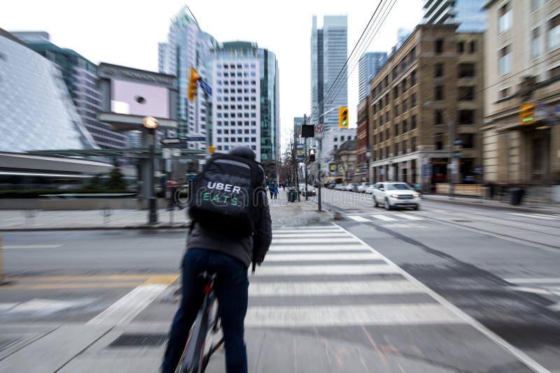 Uber在多伦多的中心,安大略吃等待的自行车的送货人穿过一条街道,与行动迷离作用 免版税库存图片