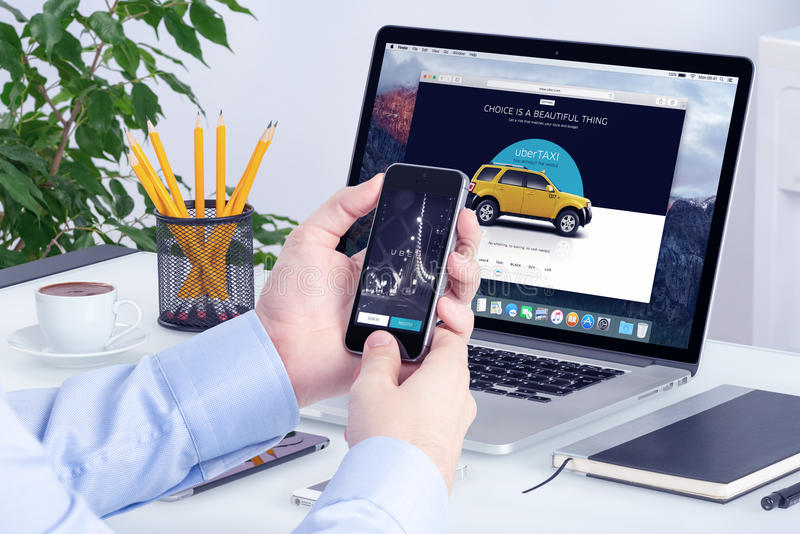 Uber app on iPhone in man hands and Uber website on Macbook Pro. Uber application on the Apple iPhone display and desktop version of Uber on the Apple Macbook