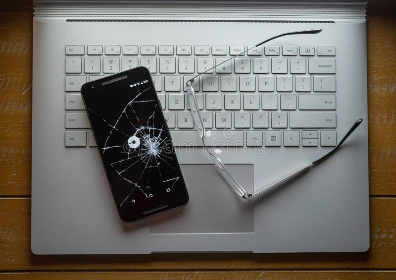 Uber app su un telefono cellulare rotto che si siede su un computer portatile accanto ai glas fotografia stock