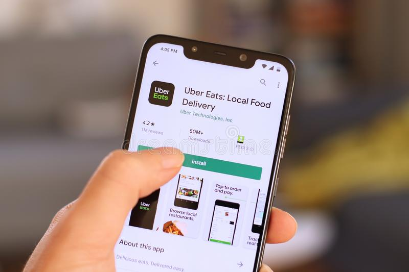 Uber Eats app. WARSAW, POLAND - OCTOBER 22, 2019: User installing Uber Eats food delivery app on a Xiaomi F1 Pocophone smart phone royalty free stock photos