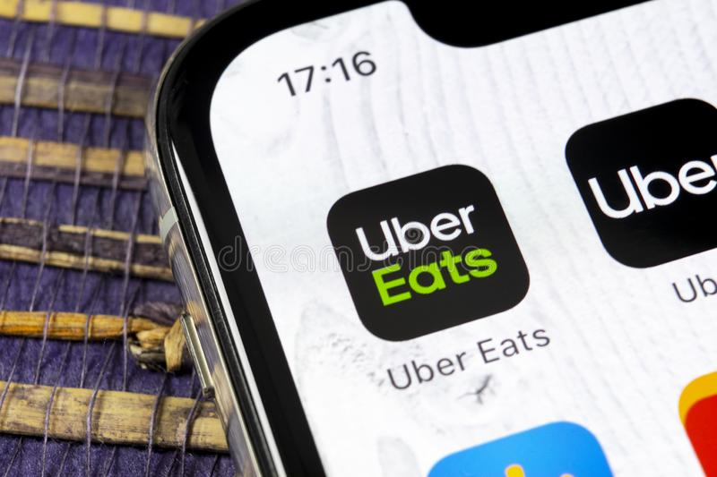 Uber Eats application icon on Apple iPhone X smartphone screen close-up. Uber eats app icon. Social network. Social media icon royalty free stock image