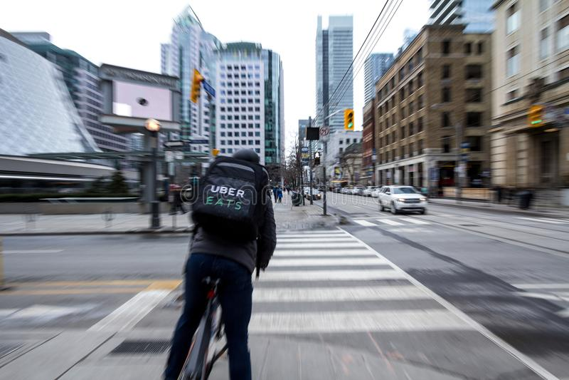 Uber mangia il fattorino su una bicicletta che aspetta per attraversare una via nel centro di Toronto, Ontario, con un effetto de immagine stock libera da diritti