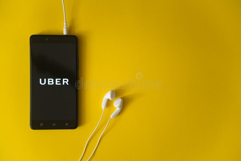 Uberembleem op het smartphonescherm op gele achtergrond stock fotografie