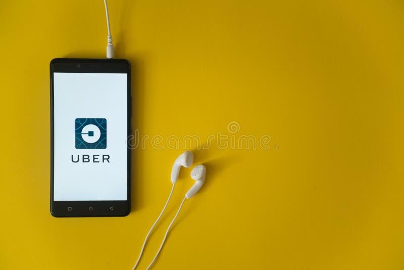 Uberembleem op het smartphonescherm op gele achtergrond stock afbeelding