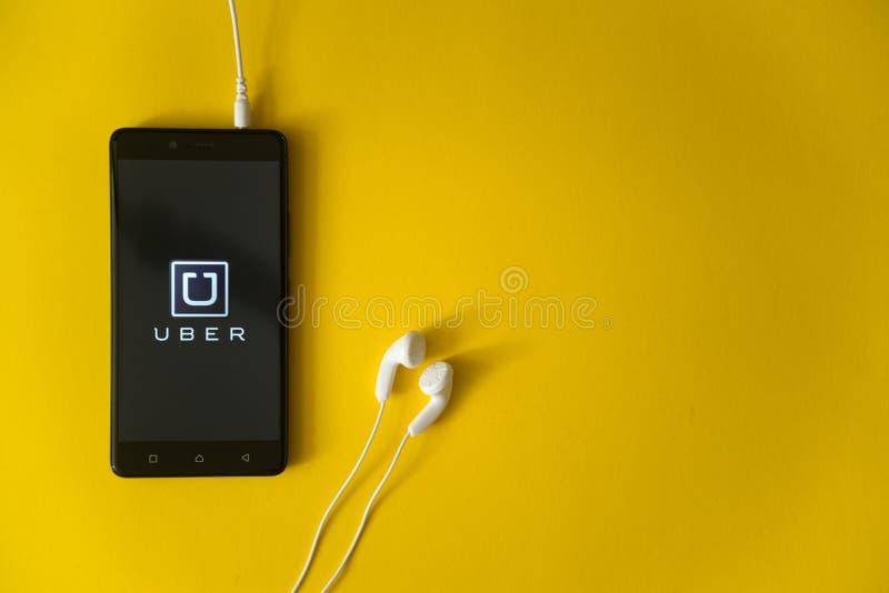Uberembleem op het smartphonescherm op gele achtergrond royalty-vrije stock foto's