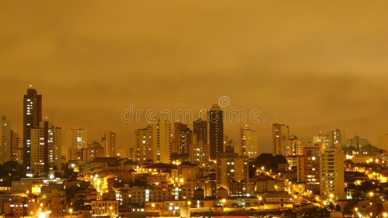 Uberlandia, Бразилия, взгляд во время дождя в ноче, желтого неба стоковая фотография