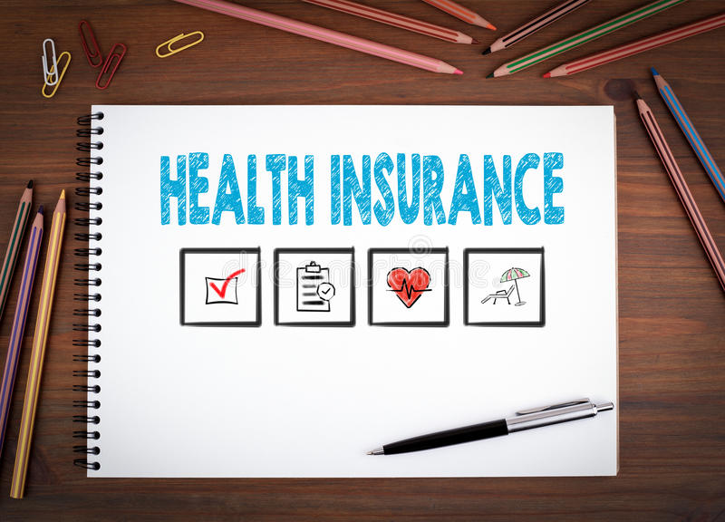 Ubezpieczenie zdrowotne Notatniki, pióro i barwioni ołówki na drewnianym stole, obraz royalty free