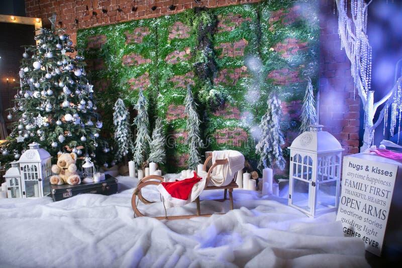 Ubicación maravillosa de la Navidad con la imitación de la nieve, carámbanos, árbol de navidad adornado, los trineos de los niños imagen de archivo libre de regalías