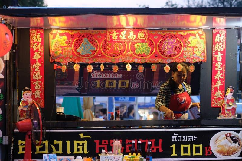 Ubon Ratchathani Thailand-Juli 17, 2019: Säljaren lagar mat kinesisk mat som är till salu till kunder arkivbild