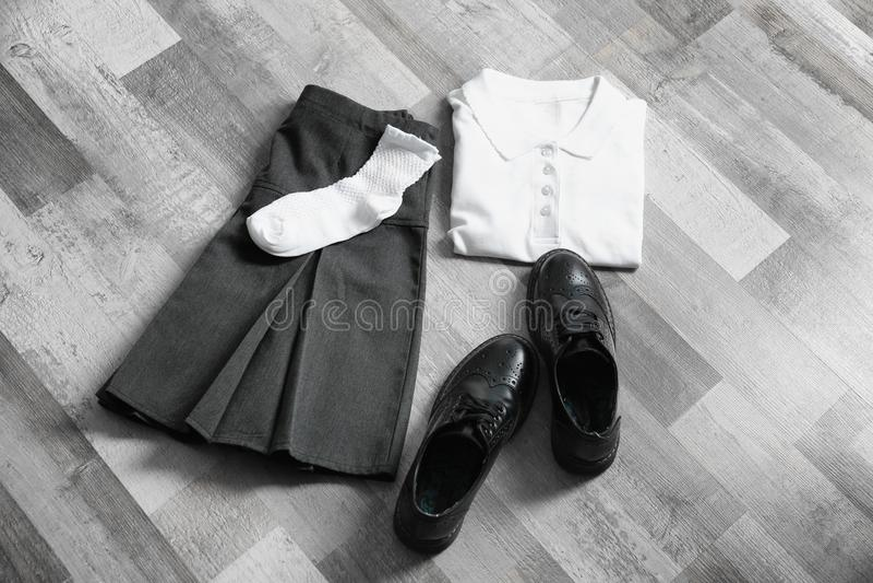 Ubrania uczennica na drewnianej podłoga zdjęcie stock