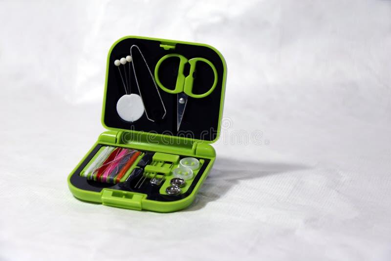 Ubraniowy naprawa set, nożyc cążki szpilek igły niciani guziki, i broszka w zielonym małym złącza pudełku zdjęcie stock