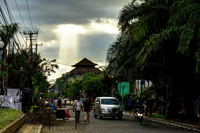 Ubud巴厘岛与阳光和人走的街场面 免版税库存图片