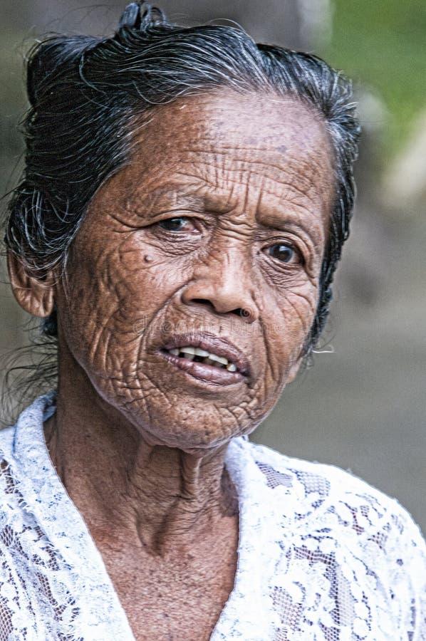 Ubud,印度尼西亚- 2013年7月28日 一位在早晨` s期间的未认出的巴厘语米非常老农夫姿势在Ubud附近运作, 免版税库存照片