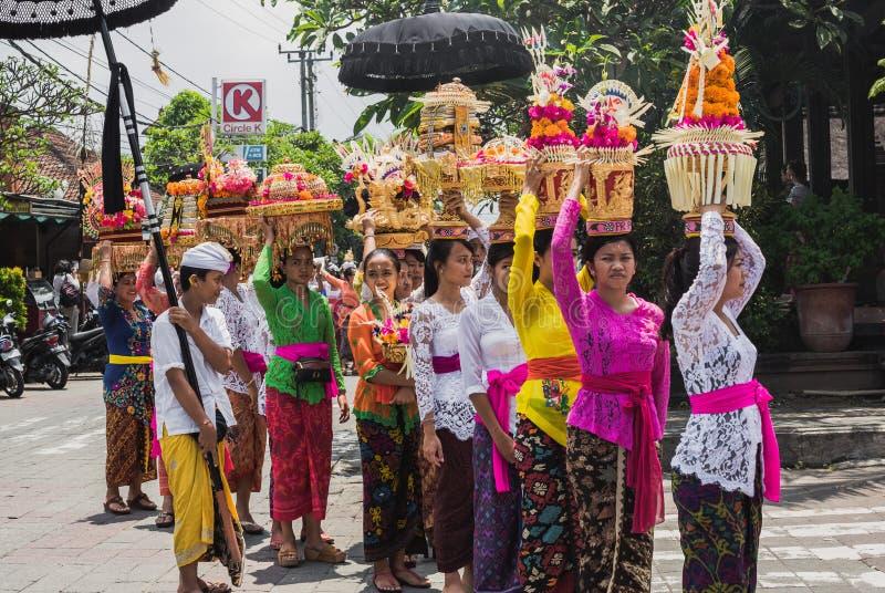 UBUD,巴厘岛- 3月8 :村庄妇女运载奉献物 免版税库存图片