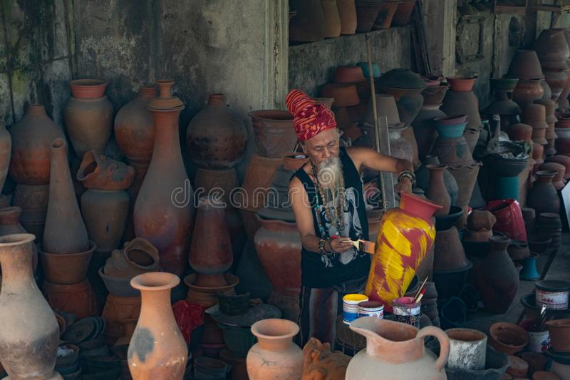 UBUD, BALI-APRIL 27 2019-an old white-bearded pottery craftsman wearing an ethnic head tie is coloring his pottery in his pottery stock images