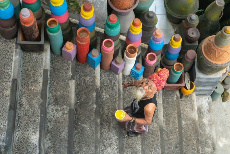 UBUD, BALI 27 AVRIL 2019 un vieil artisan blanc-barbu de poterie portant une cravatte principale ethnique colore sa poterie en sa photos stock